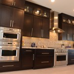 kitchen design with dark stained wood cabinetry and stainless steel appliances