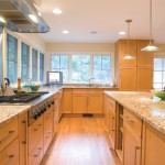 Stone countertops and island in kitchen with natural wood cabinets and lots of windows
