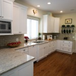 Long kitchen design with stone countertops, white cabinets
