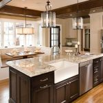 Open kitchen with farmhouse sink, granite countertops, dark wood cabinets and breakfast nook