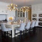 Large kitchen with white kitchen cabinets, gold chandeliers and island with bar stools
