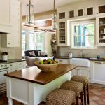 Kitchen with white cabinets and island with stools