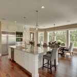 Open Kitchen and dining with white cabinets and large island with chairs
