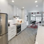 kitchen remodel with stainless steel fridge and white painted cabinetry
