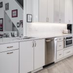 kitchen design with white cabinetry and red framed pictures