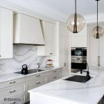 Cream and white kitchen with Brittanicca quartz countertops and black faucet and sink