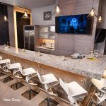 New-Quay Quartz Countertops with white stools and TV in kitchen
