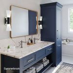 The summerbrook quartz countertops show a lovely veining against the gold fixtures and blue cabinets in this bathroom design