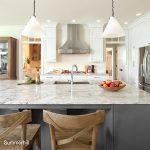 The summerhill quartz countertops and quartz island shine bright against the stainless steel, gray island and white cabinets in this kitchen design