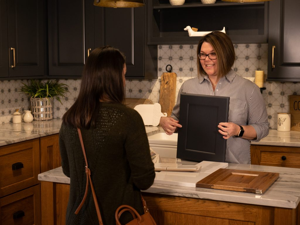 Kitchen and Bath Designers at Benson Stone help pick out cabinets for customer