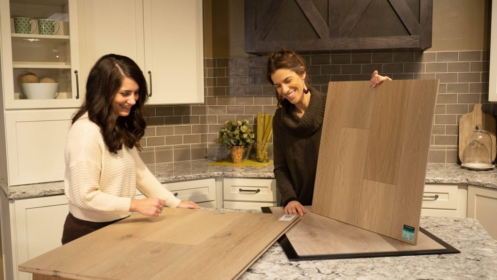 Benson Stone Flooring Designers help customers find the perfect hardwood for their kitchen by comparing granite and flooring samples