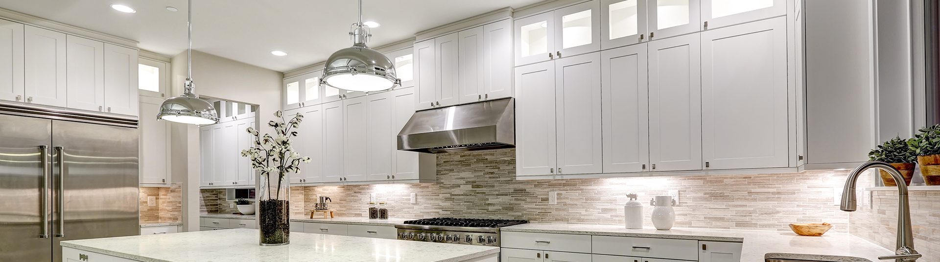 White kitchen cabinets with stainless steel appliances in beautiful, clean kitchen