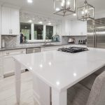 snowy white quartz kitchen countertop with built-in stove on island