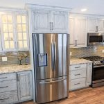 granite countertops in a kitchen with a stainless steel fridge