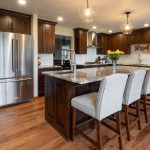 Kitchen remodel featuring wood cabinetry, granite countertops, and grey upholstered bar stools