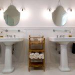 two white pedestal sinks and white tile floor