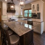 traditional kitchen remodel with granite countertops on the island and traditional glass pendant lighting