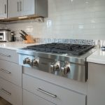 kitchen remodel with grey cabinetry and stainless steel stovetop