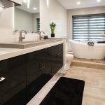 modern bathroom remodel with waterfall vanity tops and sleek black vanity cabinets