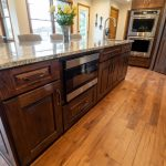 Kitchen remodel kitchen island with stained wood cabinetry and built-in microwave and hardwood flooring