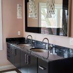 bathroom remodel with black floating vanity and black granite countertops and crystal pendant lights