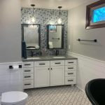 blue mosaic wall tile and white vanity cabinets