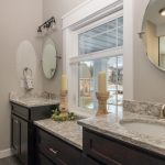 double vanity with granite countertops and dark painted cabinets